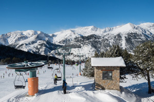 Skiing and snowboarding on the snowy slopes of prepared ski resort in Andorra